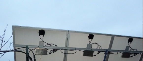 Microinverters nestled underneath each solar panel, on strengthened aluminium roof fittings