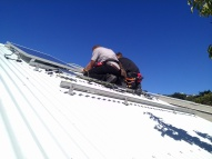 The ALOSUN team mounting the microinverters to the framing.